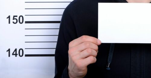 a shoulder to chest shot of a person's body (only their right hand side of the body) holding a blank white piece of paper in front of a background with height measurement lines displaying the numbers 140 and 150, insinuating a mug shot.