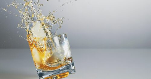 An in-action shot of a short glass with some alcohol (similar to whiskey or rum) in the middle of being knocked and the alcohol is splashing out of the glass.