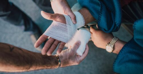 A photo of two people's hands. A person's right hand is being bandaged with a white bandage by another person to heal an injury.