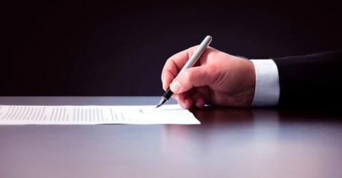 A side photo of someone's right hand holding a fountain pen and signing a piece of paper.