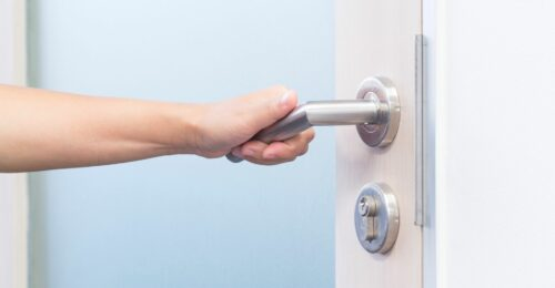 A close up photo of a person's left hand opening up a door by turning a silver door handle.