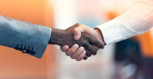 A side close up photo of 2 men shaking hands.