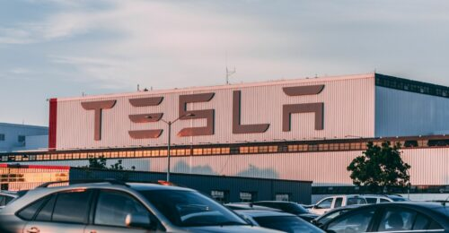 A photo of a tesla warehouse from the front, showing clearly, the Tesla company name.