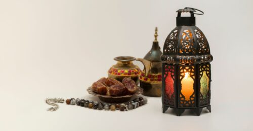A photo of a bronze lit up lantern, and some utensils of a middle east style, with some dates sitting in a brass bowl.