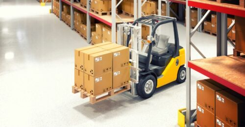 A photo of a small yellow forklift in a warehouse carrying 8 cardboard boxes.