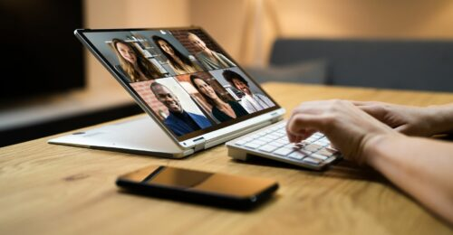 A photo of someone typing on a keyboard with their computer screen full of 6 people's faces as they video call.