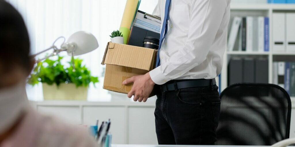 A half body shot of an employee holding a box of items after being terminated.